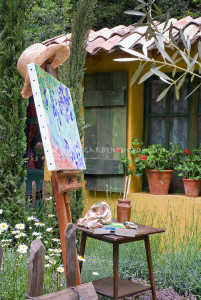 Artist's easel outdoors in the spring May June garden with painting, next to house with shutters, window, flowers, irises aka van Gogh, painting supplies, pot containers, shasta daisies, herbs in rustic garden of flowers and herbs